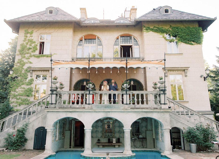 Bride and Groom waving from the Balcony at The Writer's Villa, Budapest